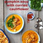 Two bowls of pumpkin soup with cauliflower and some parsley leaves, laid out on a wooden board
