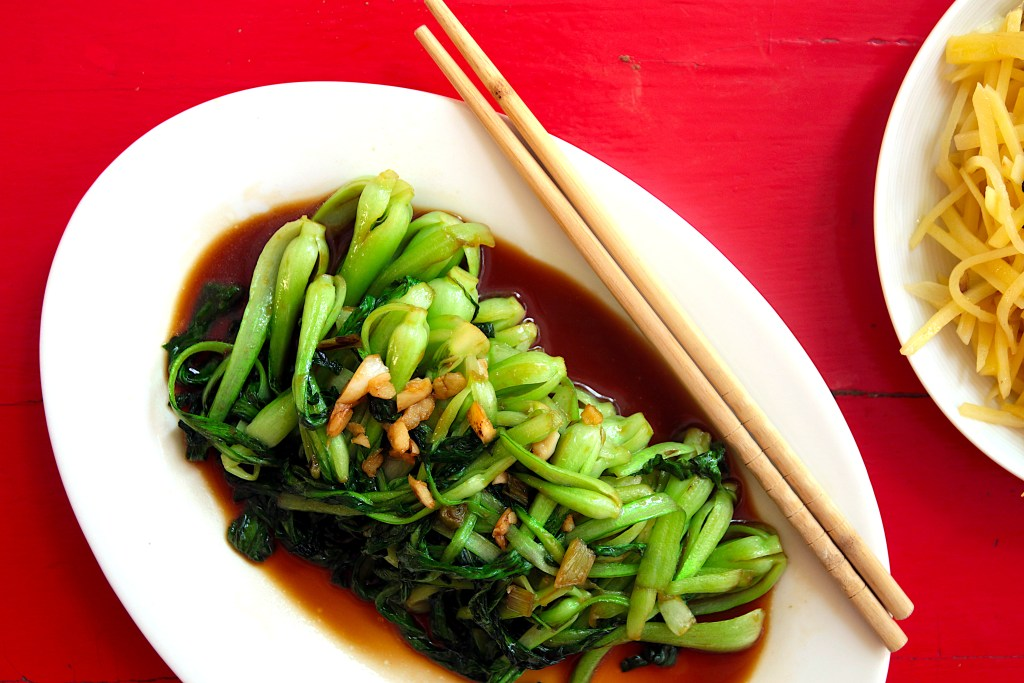 a white serving plate with stir fried bok choy with chopsticks on a red table