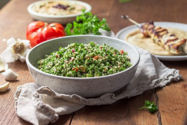 Cauliflower tabbouleh with parsley and tomatoes served with grilled chicken kebab.