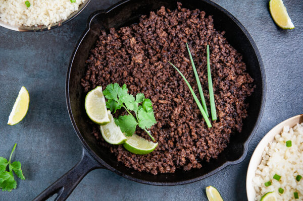 Ground beef with Korean flavors in a skillet with lime, cilantro and scallions.