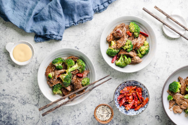 Keto beef and broccoli with dried red peppers in bowls with chopsticks and Chinese mustard.