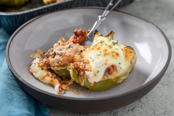 stuffed green bell pepper with meat and cheese in a bowl with fork