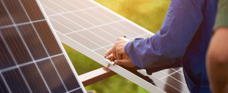 man working on a solar power mounting with pencil
