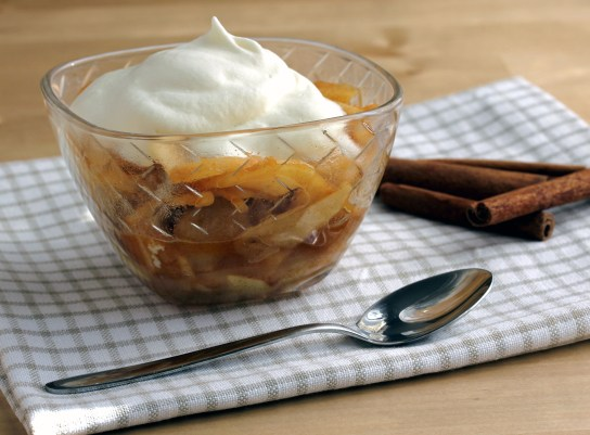 Sauteed Apple Slices With Whipped Cream, in a Dessert Bowl, Spoon and Some Cinnamon Sticks