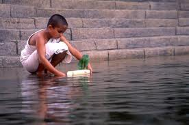 Boy monk at temple pond