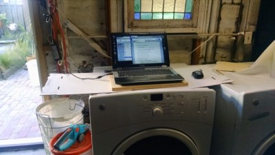 A clothes dryer under a window with a wood plank desktop supporting a laptop.