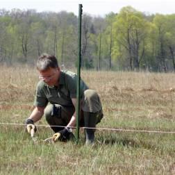Christian Niederbichler kürzt das Gras, damit der Strom besser fließt.