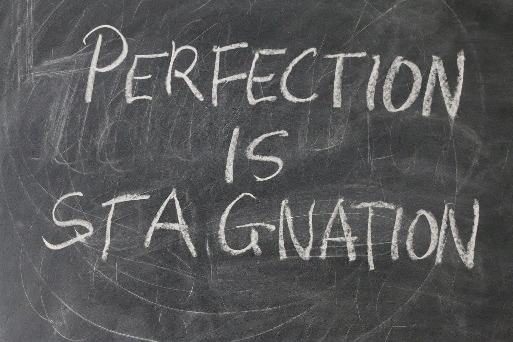 chalkboard with words perfection is stagnation