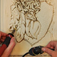 Wood burning the stop cuts of a wood carving relief