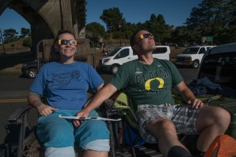 2 people using special eclipse chaser sunglasses to watch the solar eclipse. Photo: Keith James