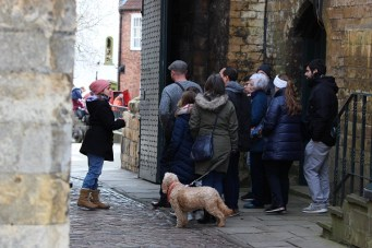 Dog stands with owner on guided tour