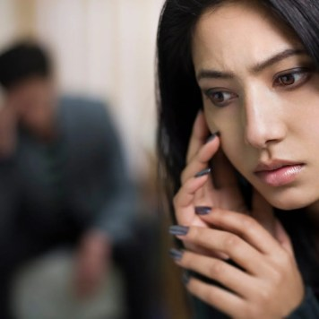 Image of a person with long black hair on the phone. They look dismayed and tense. To the left of them is a blurry image of their partner, expressionless and fading in the background. This image represents the fear have that their relationship(s) or future relationship(s) may be bleak because of their Lichen Sclerosus diagnosis.