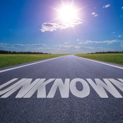 """Image of a road stretching out into the horizon. The words """"Unknown"""" are sprawled out in the middle of the road in big blocky white letters. There is a blue sky with a sun and some clouds above. This image represents the fear of the unknown."""