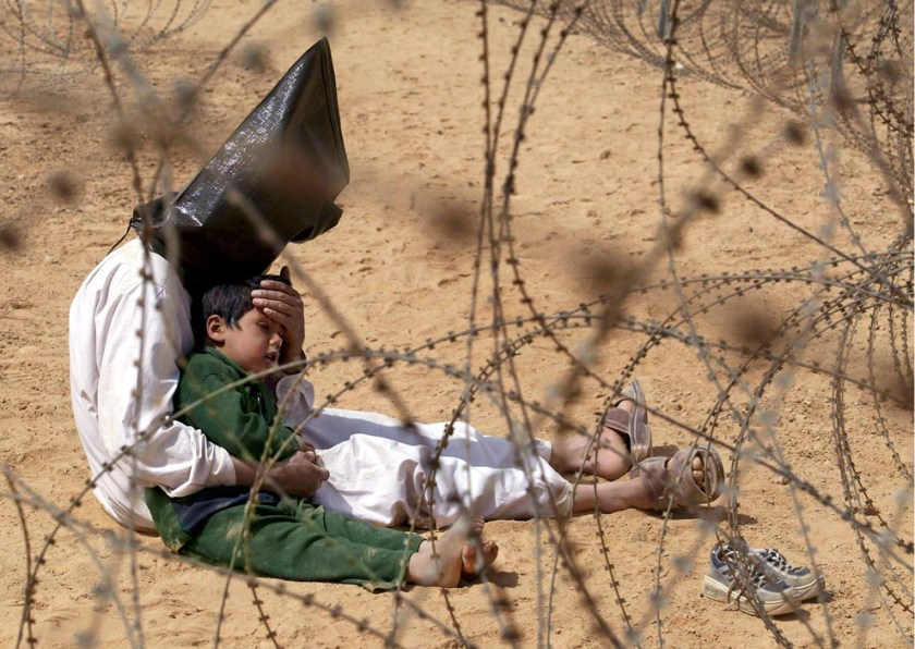 An Iraqi prisoner of war comforts his 4-year-old son at a regroupment center for POWs of the 101st Airborne Division near An Najaf, Iraq in this March 31, 2003 file photo. The man was seized in An Najaf with his son and the U.S. military did not want to separate father and son. (AP Photo/Jean-Marc Bouju, File)