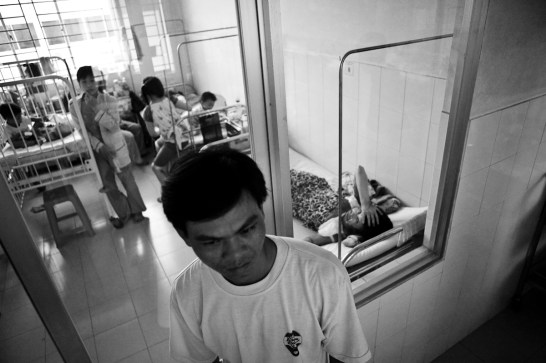 The husband of the burn victim awaits outside her hospital room. Danang. Vietnam. 2007