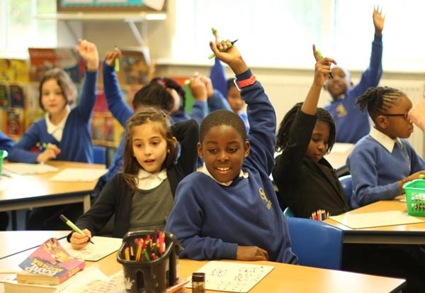 Class with their hands up during a lesson