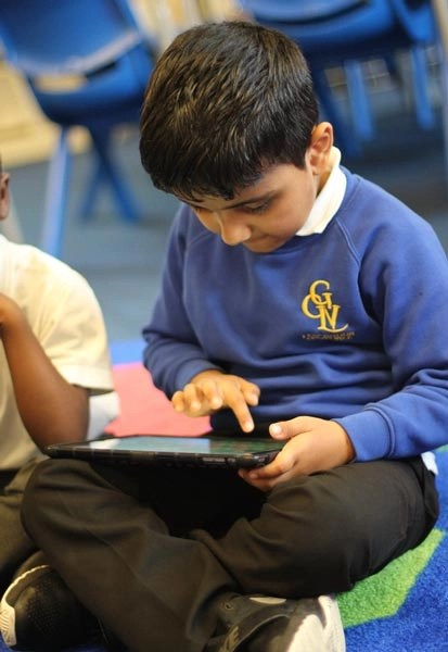 Young boy looking at an iPad at the After School Club