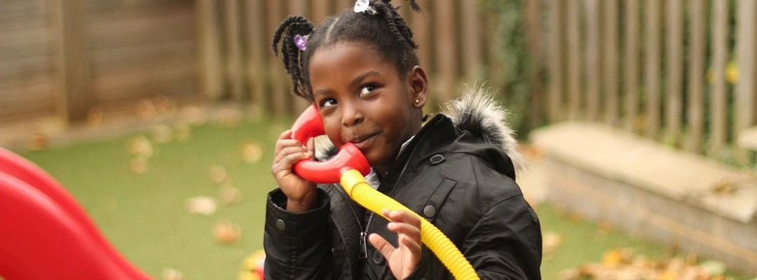 Girl playing with toy telephone at the Breakfast Club
