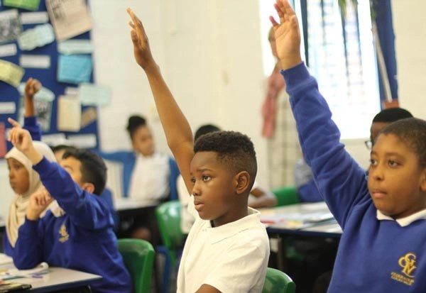 Children with their hands up during a lesson