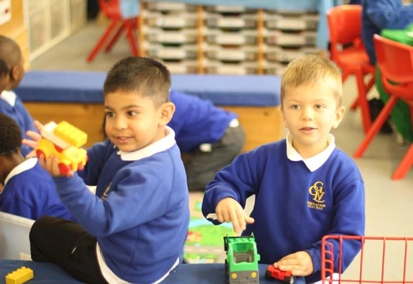 Two boys building cars from building blocks
