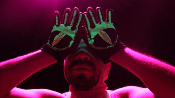 Imagen con una escena de la obra deshojado donde el actor pone sus manos con las palmas con pintura imitando la forma de un iris y los dedos pintados como un pelo de pestaña frente a sus ojos para simular los mismos abiertos