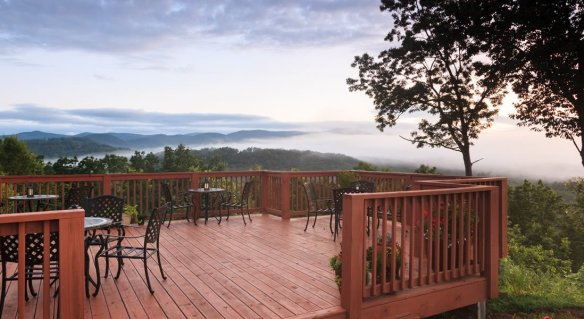 The deck off of the inn with table and chairs and you can see for ever mountains and clouds