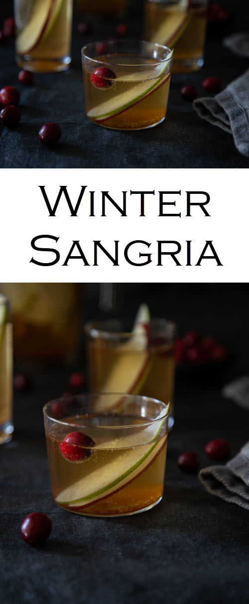 White Wine Winter Sangria w. Apples, Pears, + Cranberries. This spiced sangria is a perfect fall and winter cocktail made with traditional holiday spices. Serve this as a Christmas Sangria! #lmrecipes #sangria #cocktails #christmas #christmasrecipes #whitewine #foodblog