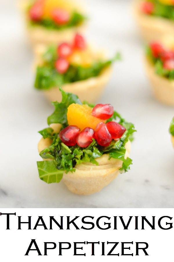 Mini Bite Size Thanksgiving Appetizers. A delicious kale salad recipe with pomegranate seeds and orange segments, this mix is great for any holiday meal. Place salad bits in homemade mini tart crusts for festive bite size appetizers. #LMrecipes #salad #thanksgiving #friendsgiving #kale #pomegranate #bitesize #holidays #christmas #appetizers #partyfood