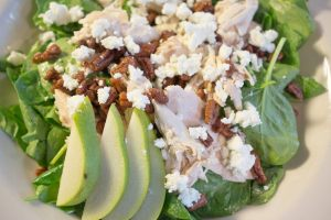 Roasted Chicken Salad with baby spinach, Goat Lady chèvre, sliced pear and spiced pecans tossed with Jeanne Edward's poppyseed vinaigrette