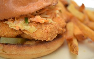 Snappy Chicken Sandwich, cornmeal-fried chicken breast on a challah bun with housemade Pig & Whistle sauce, pickles and slaw