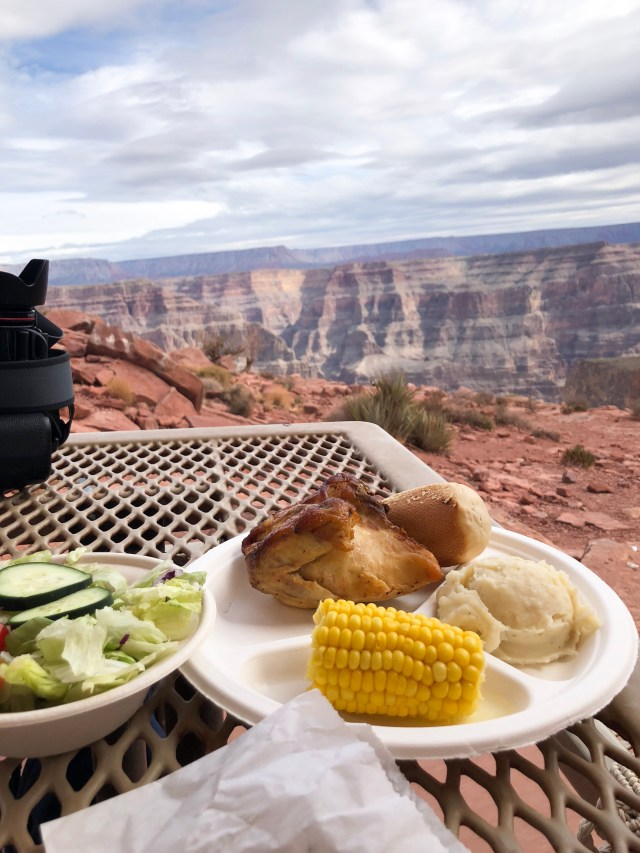 Photo of a bbq lunch consisting of chicken salad mash potatoe and corn on the cob ontop a table with a view of the Grand Canyon in the back ground