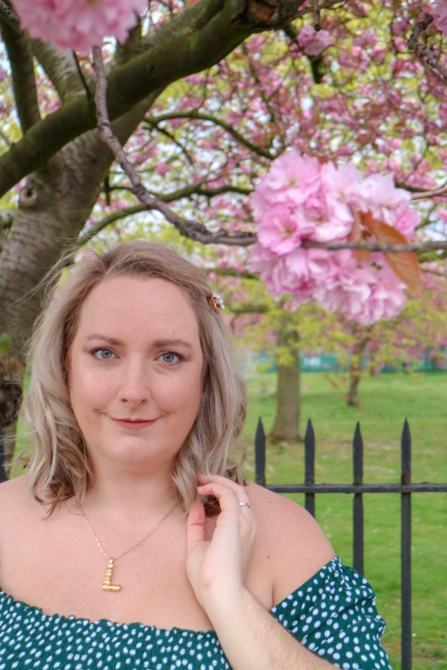 lucy with grey hair stood in front of a blossom tree