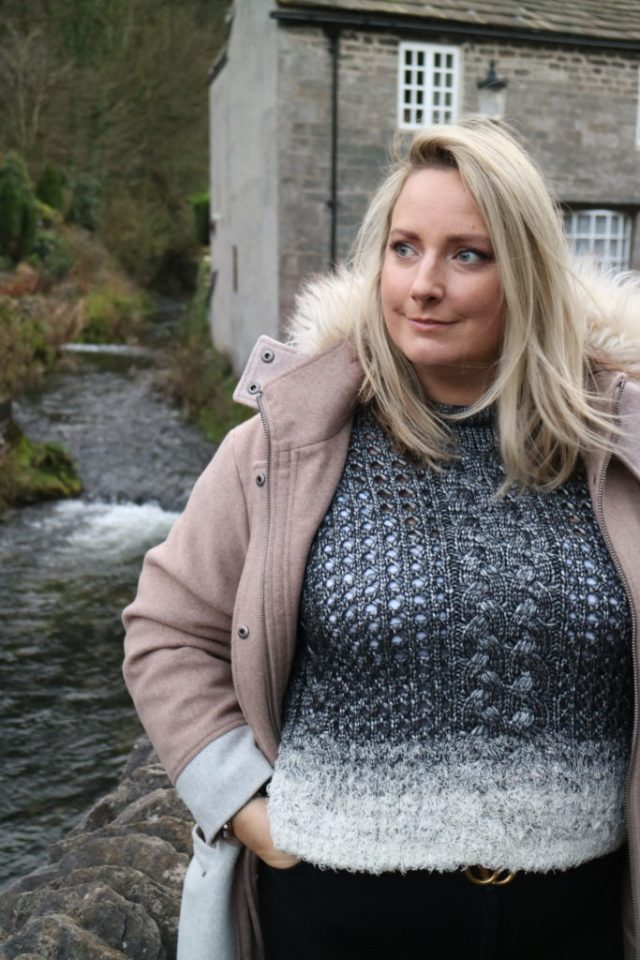 Lucy in a grey topshop jumper and pink asos coat stood on a bridge with a house in the back ground