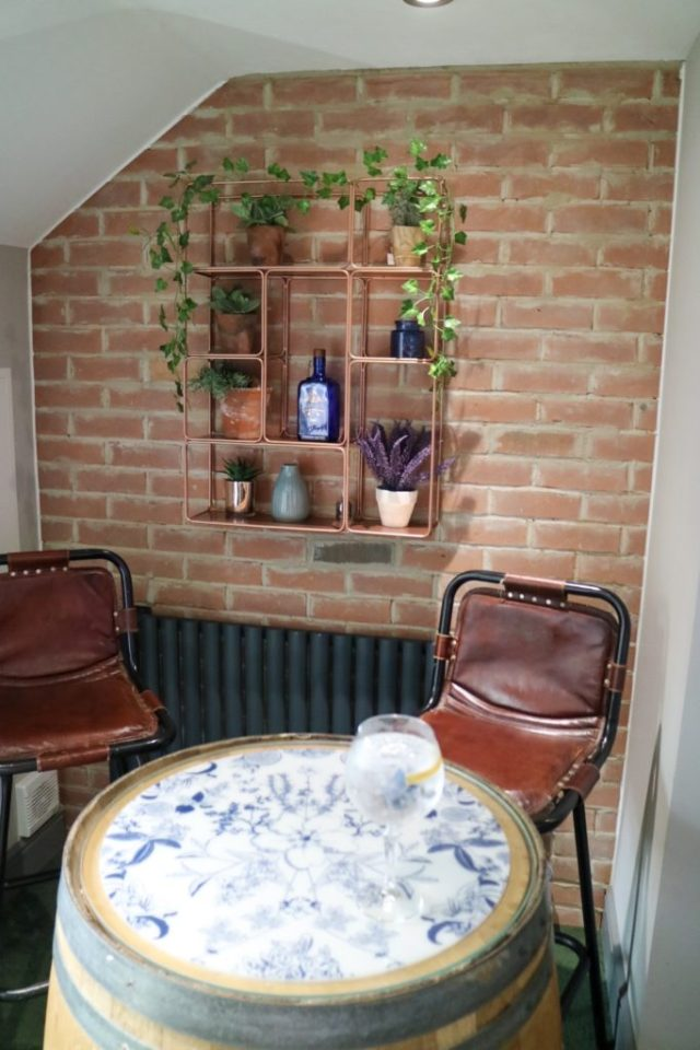 two high stools and table with a brick wall and shelves