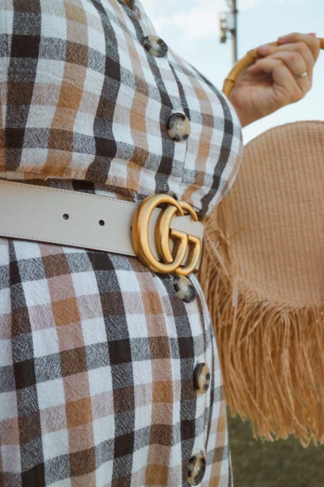 Gucci Belt White GG logo against a check dress and straw bag
