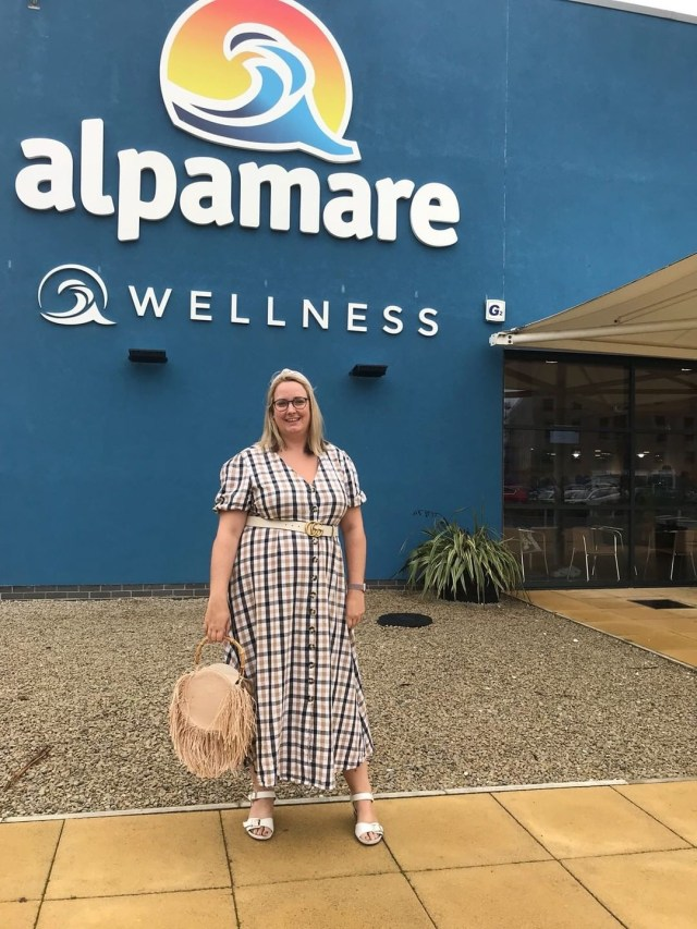 lucy in a check maxi dress stood in front of the alpamare sign