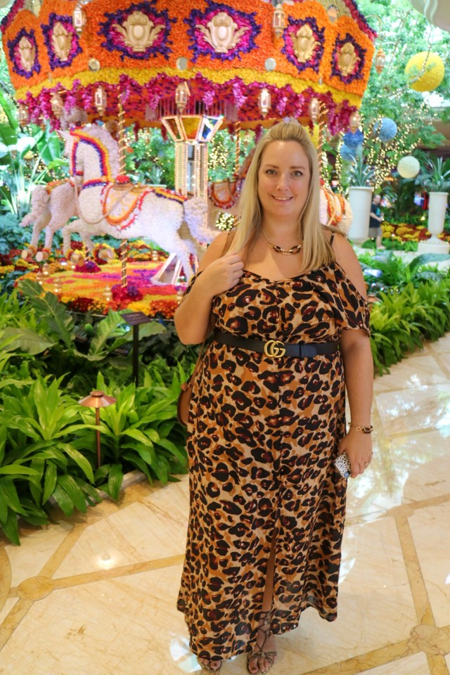 lucy in a leopard print dress in front of a flroal carousel display in The Wynn Las Vegas