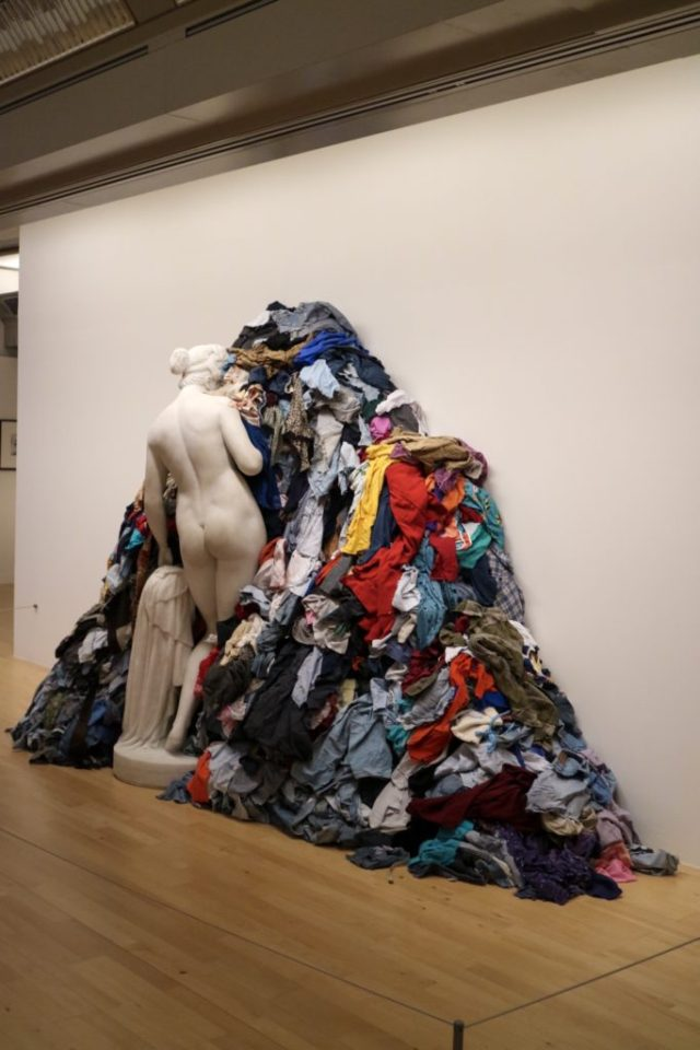 art at the tate liverpool- a statue facing the wall surrounded by scraps of clothes