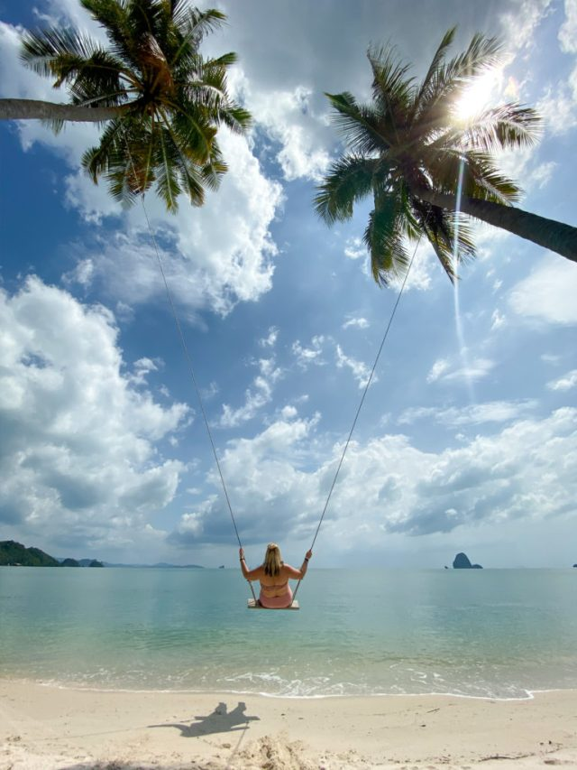 lucy on the sea swing between two palm trees