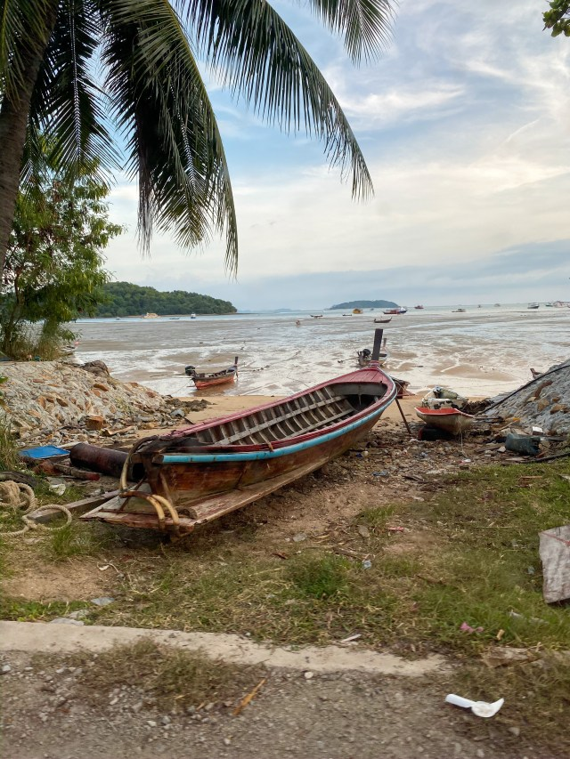 on old thai boat moored up on the shore