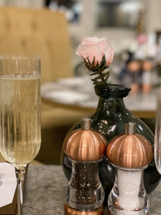 glass of champagne and rose in a vase with salt and pepper shakers in front