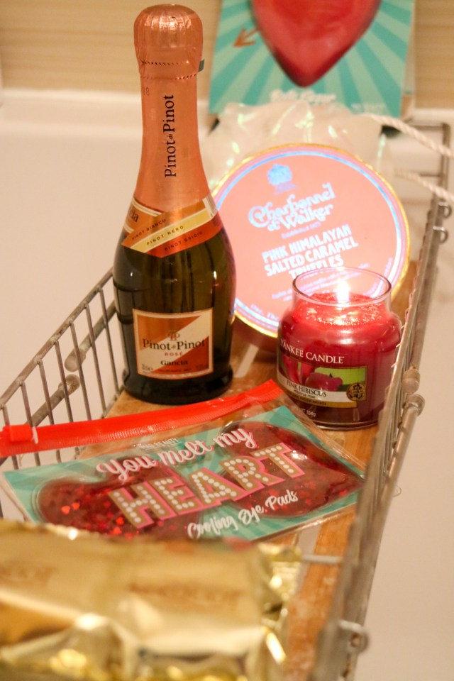 small rose prosecco, truffles and candele on a bath tray