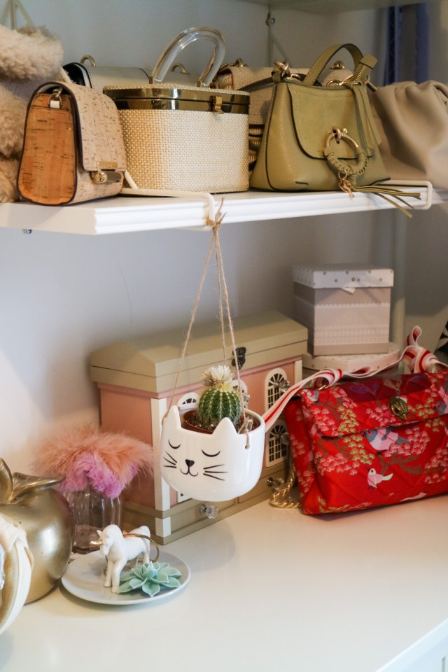 hanging cat planter beneath a shelf of handbags