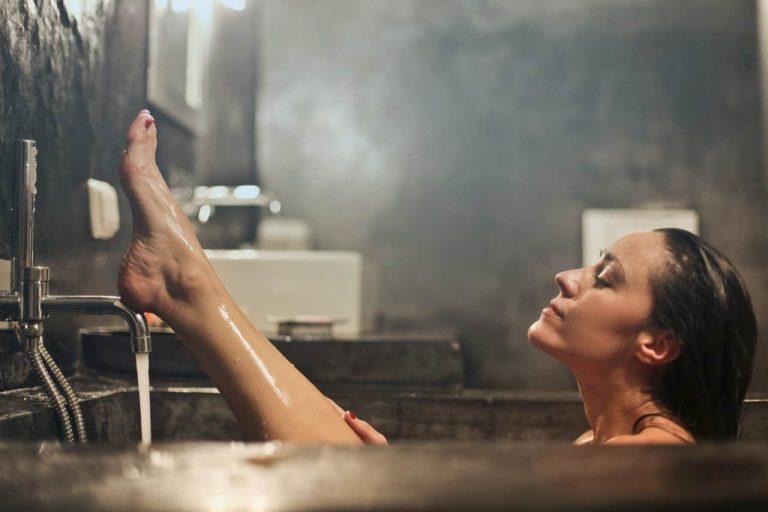 Frau in Badewanne mit dampfender Luft