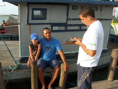 Sentado, o pescador Francisco de Oliveira e seu filho