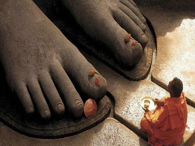 Monge budista medita aos pés de estátua gigante do Buda