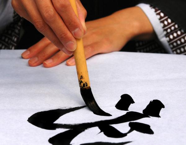 Calígrafo chinês desenha o ideograma Wei-Ji.