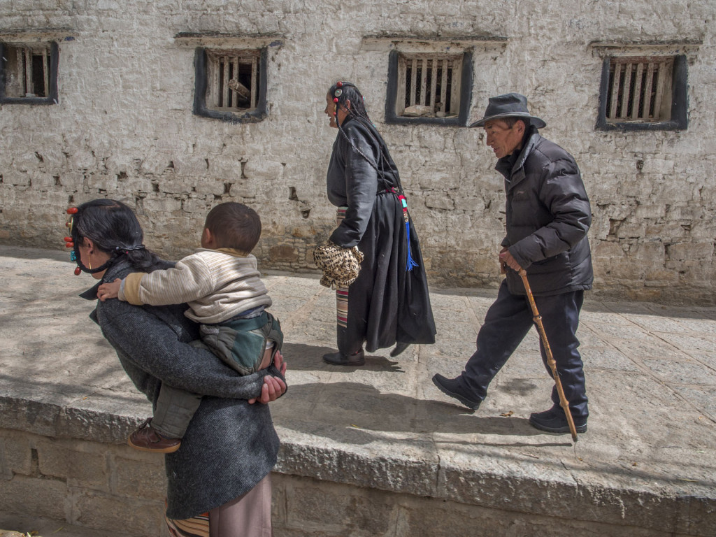 Photos ©Jay Dickman, 20131022_ATW_Tibet_03325F Three pilgrims walking with baby to Monastery in Tibet (306 words) Photographing people is what I love doing most. The on-going ÒdanceÓ in front of the camera is never repeated and ÒmomentÓ is paramount, as it brings the energy to the viewer. I think the job of a photographer is almost that of a director or choreographer. We set the stage and wait for our subjects to reach their peak moment. ItÕs the responsibility of the photographer to capture that moment, loud or quiet. I was photographing in Lhasa, Tibet around Norbulingka Park, the former summer palace of the Dalai Lama. Walking in those grounds, I headed towards Drepung Monastery, when I saw these three pilgrims on their quest to visit the monastery. Photographing people is not an easy process for everyone. Approaching a stranger, home or abroad, to ask permission to take their picture can be intimidating and for many aspiring photographers, the first time you try this it may be met with a negative response. DonÕt take it personally. IÕve found that I have about an 85%+ success rate in asking permission to photograph a complete stranger. Part of the process is to ÒreadÓ a situation, to see if itÕs appropriate to approach a potential photo subject. Why I, and other photographers are successful is this process is pretty simple; we make eye contact and show real interest in what that person is doing. They may stop doing what was cool, and turn to you to take your picture, but give the process time so you become kind of boringÉ so your subject goes back to doing what was interesting to you. You are entering a short-lived Ò relationshipÓ with that person, and your job is to capture what best illustrates what that person is about. Give this some time for the situation to develop, but also be sensitive to when youÕve overstayed your welcome. Olympus E-M1 with 12-40mm f2.8 lens 1/200th second, f 7.1 200 ISO