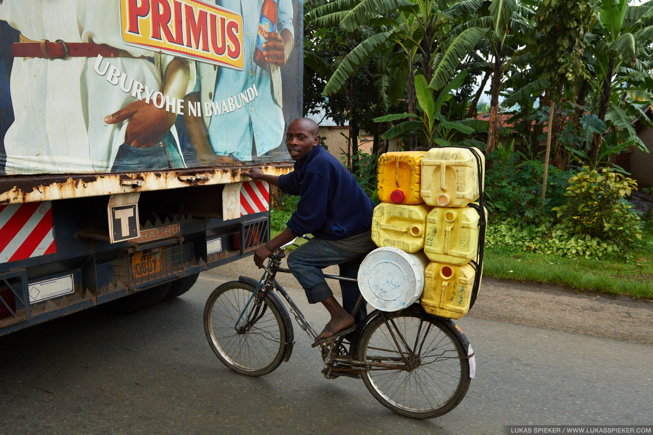 A cyclist gets a grip on a truck to let it pull him uphill. In Rwanda, the land of a thousand hills, cargo bicycles are widely used for the transportation of goods and passengers.v