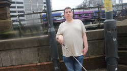 me holding a white cane.